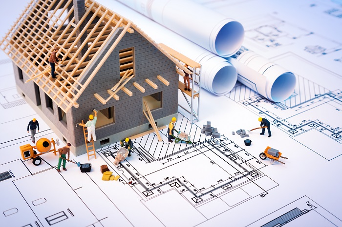 Blueprints with a small toy home sitting on top and miniature toy men working on the house.