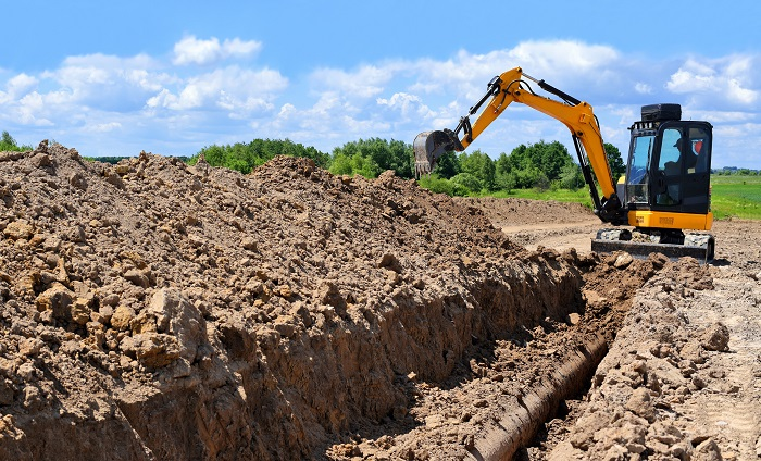 Excavator digging a trench.