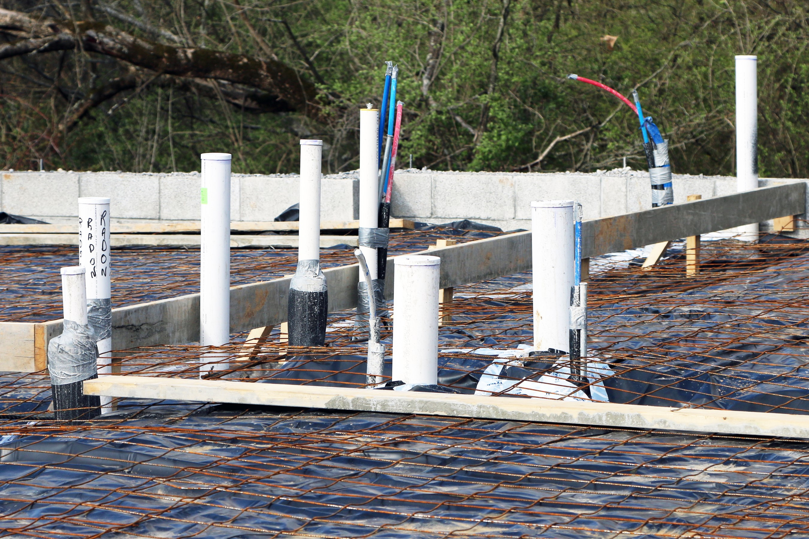 Rough in plumbing tubes above the slab concrete with rebar showing.