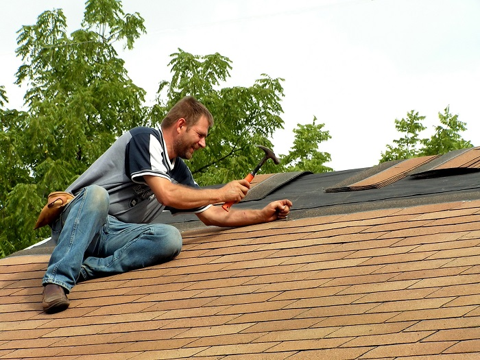 Man hammering shingles on an unfinished roof.