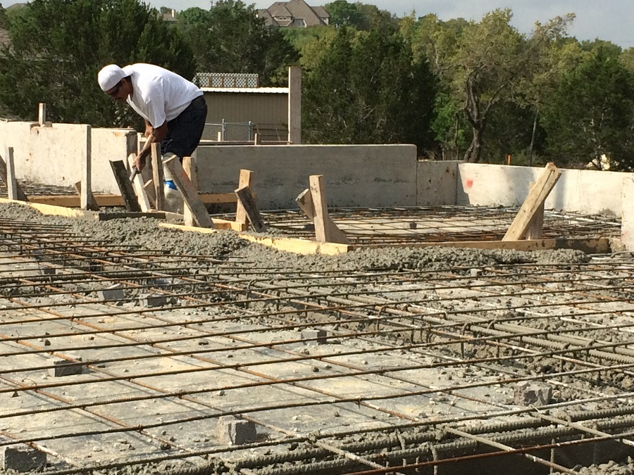Man working on a concrete foundation with rebar.