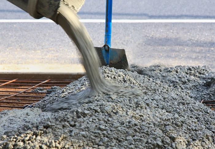 Pouring concrete into a sidewalk form.