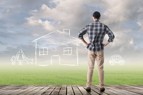 Man standing on deck looking into a field where an imaginary home is sitting.